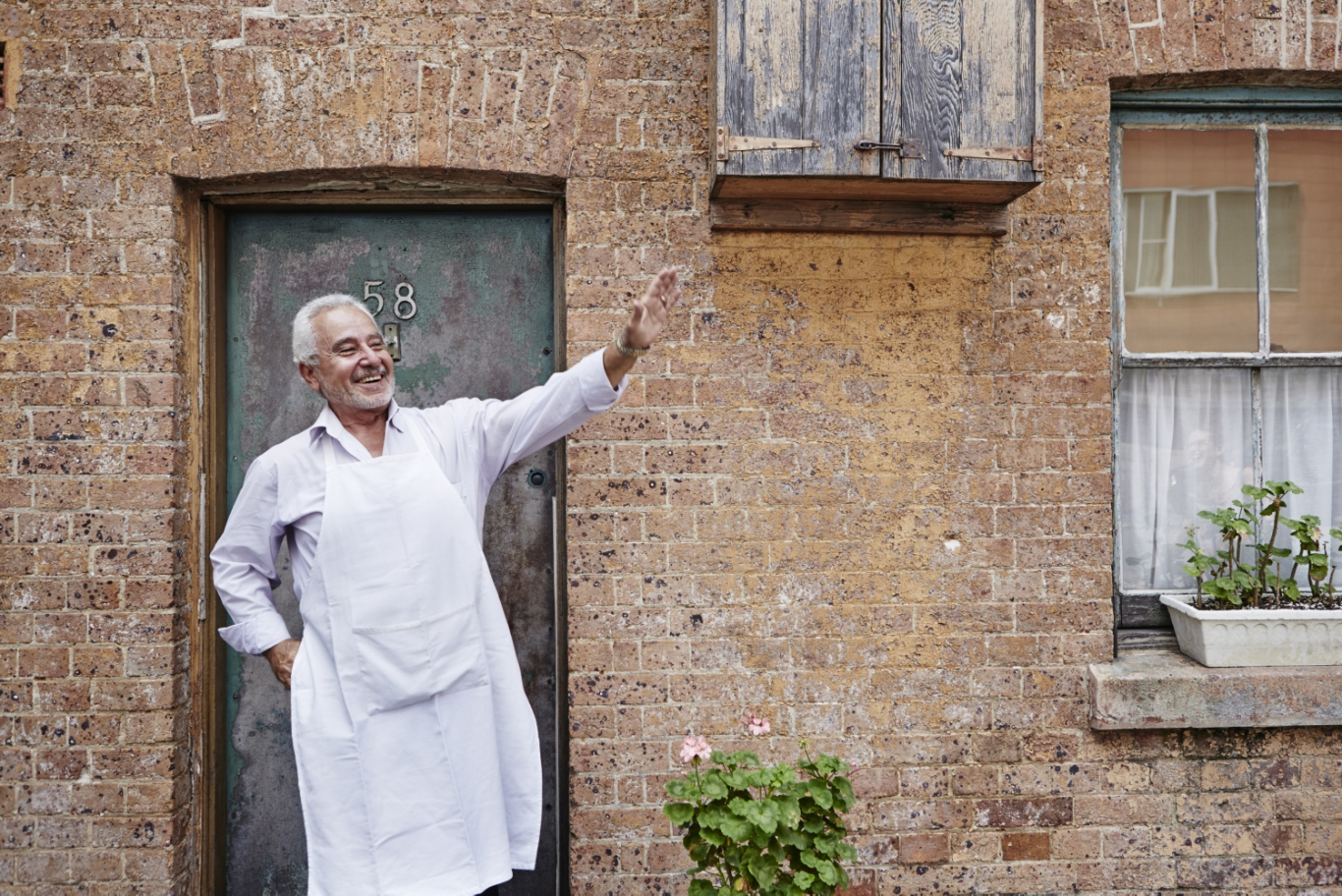 Man dressed in white waving outside front door of terrace house number 58.