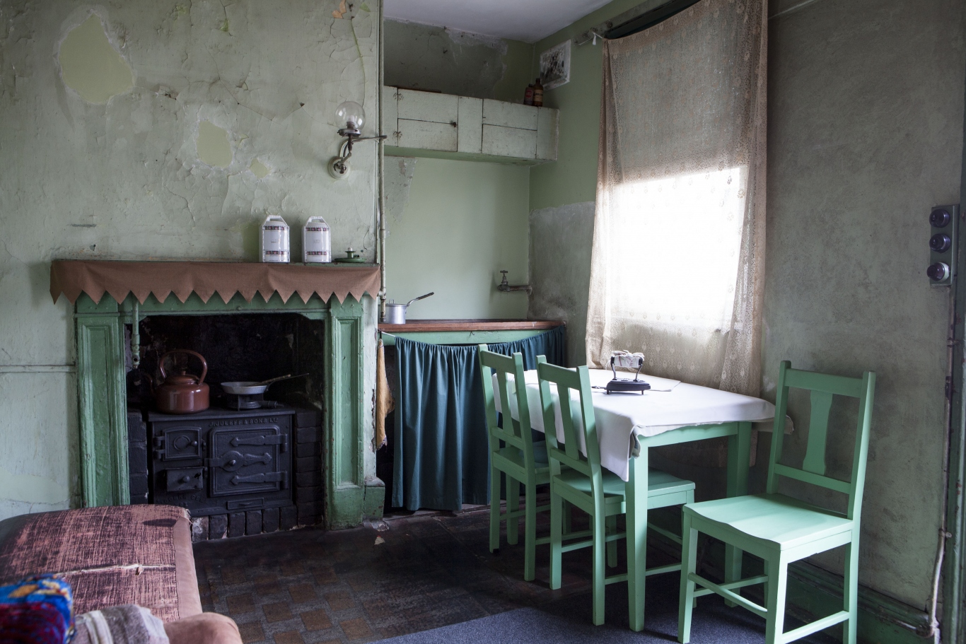 colour photograph of roughly furnished kitchen with green painted furniture, packing case cupboards besides a large fireplace with black stove inset and mantle shelf with fabric valance and containers. There's a gas bracket on the wall with a glass lamp.