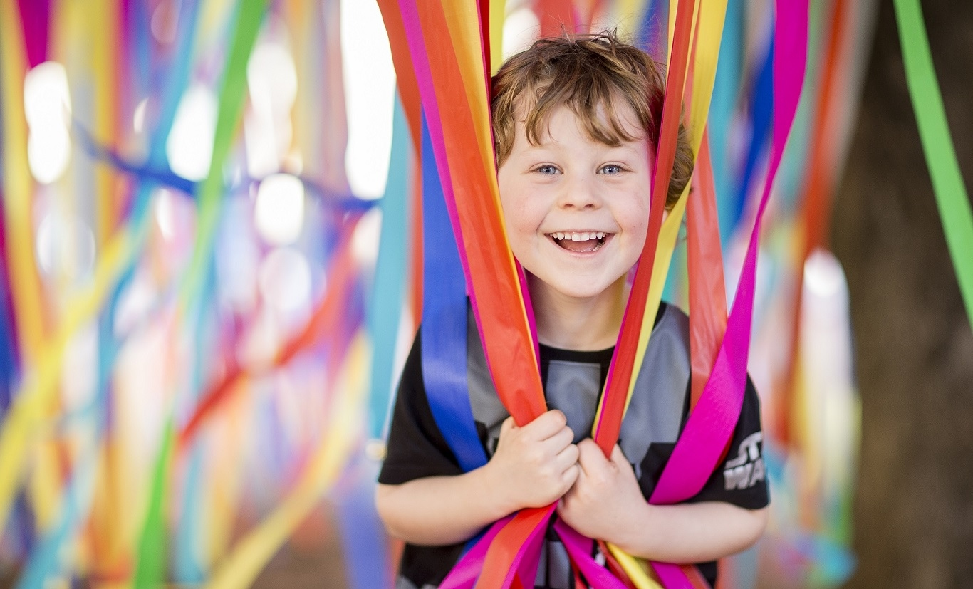 Boy with colourful streamers.
