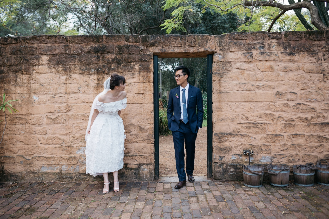 Woman and man in wedding outfits in sandstone courtyard.