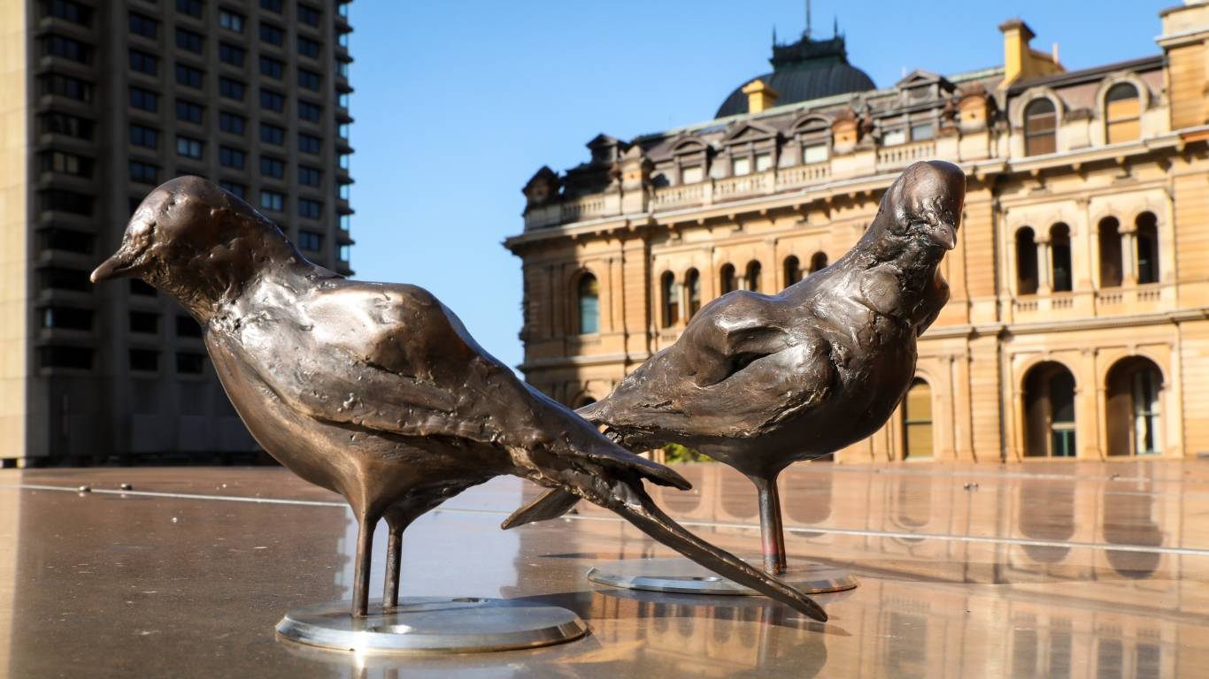Bronze sculptures of birds installed on the roof of museum.