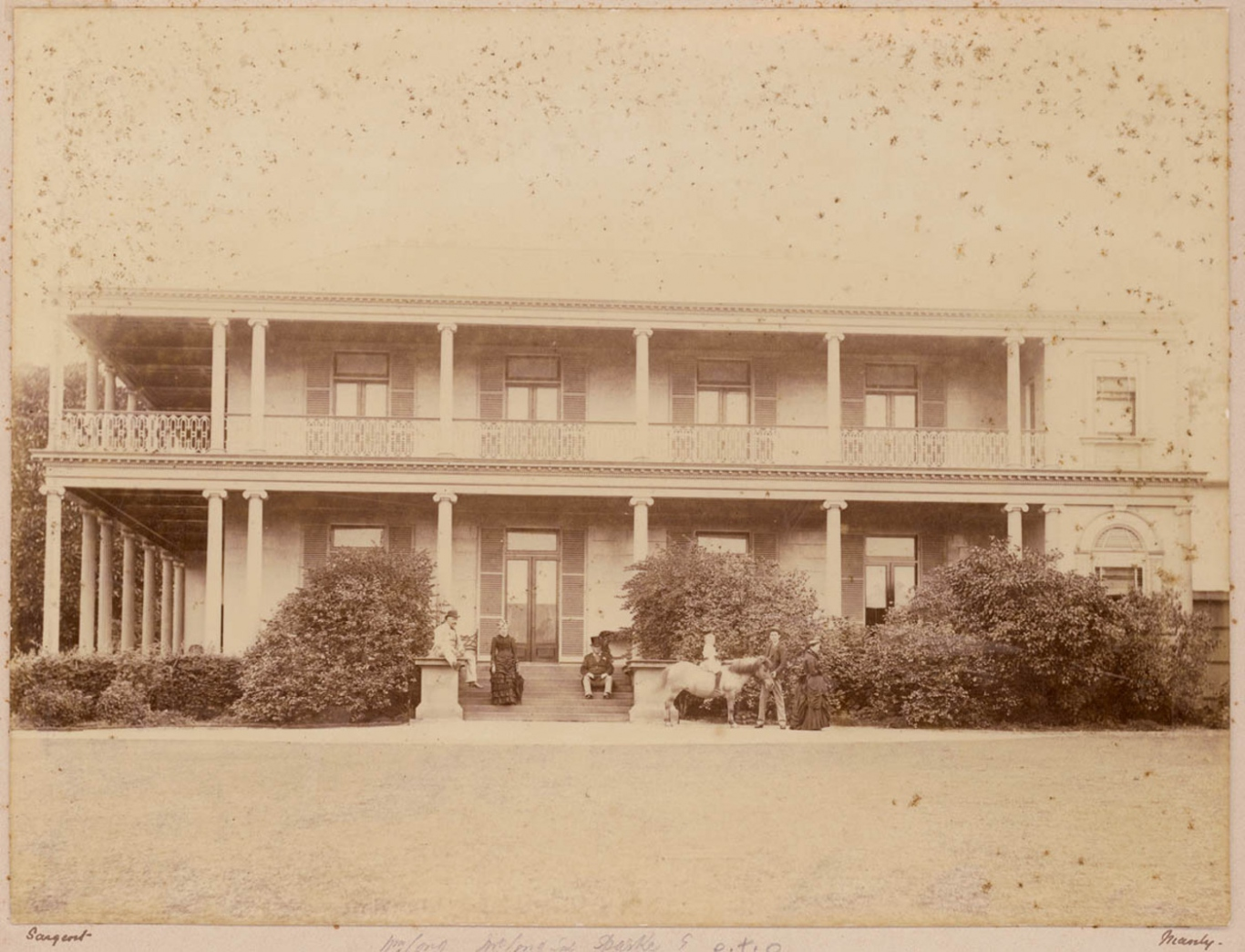 Old black and white print of two storey house with wide colonial style verandahs wrapped around it.