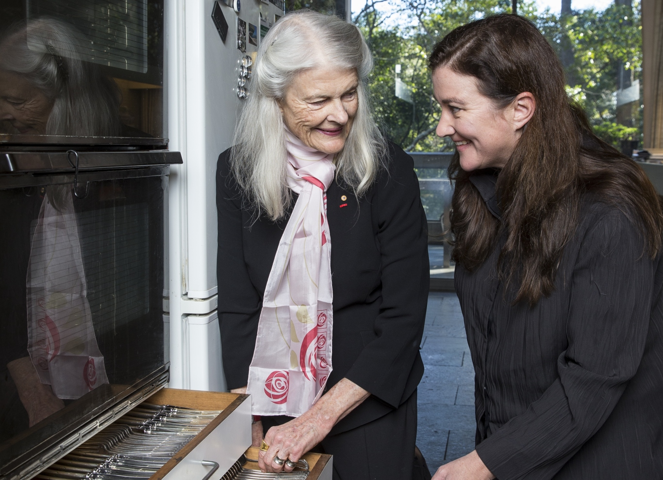 Two women smiling at each other over open cutlery display drawers.