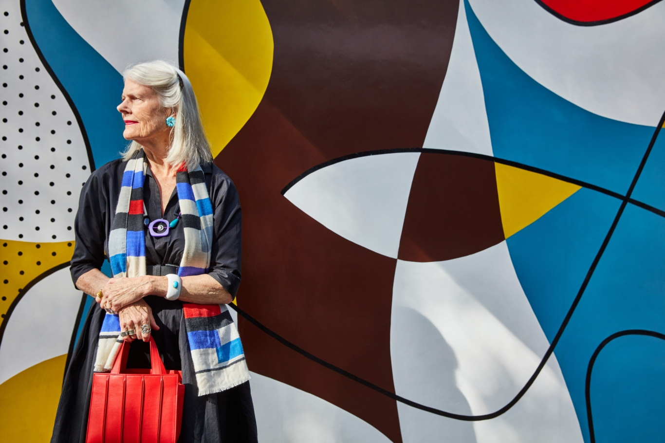 Woman standing to left of photo with brightly coloured mural behind.