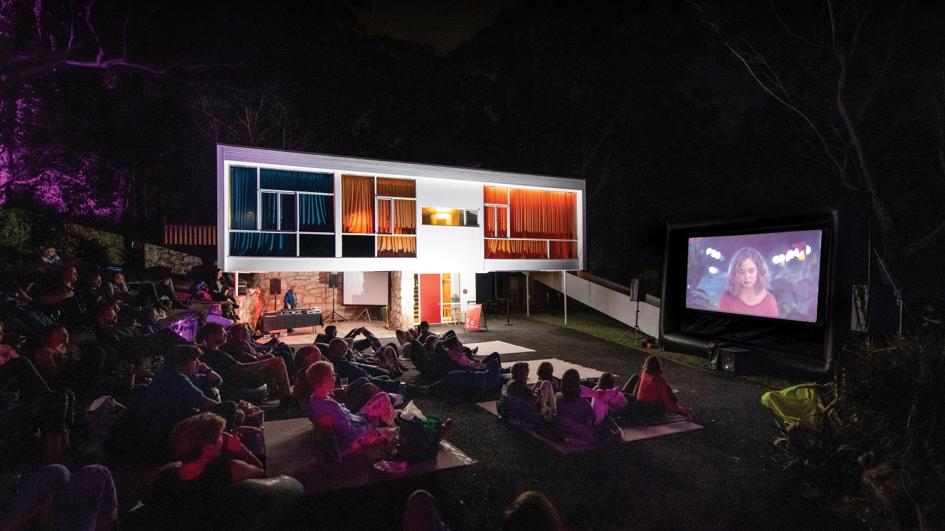 Outdoor setting at night time with modernist house and crowd seated in garden with movie on screen.