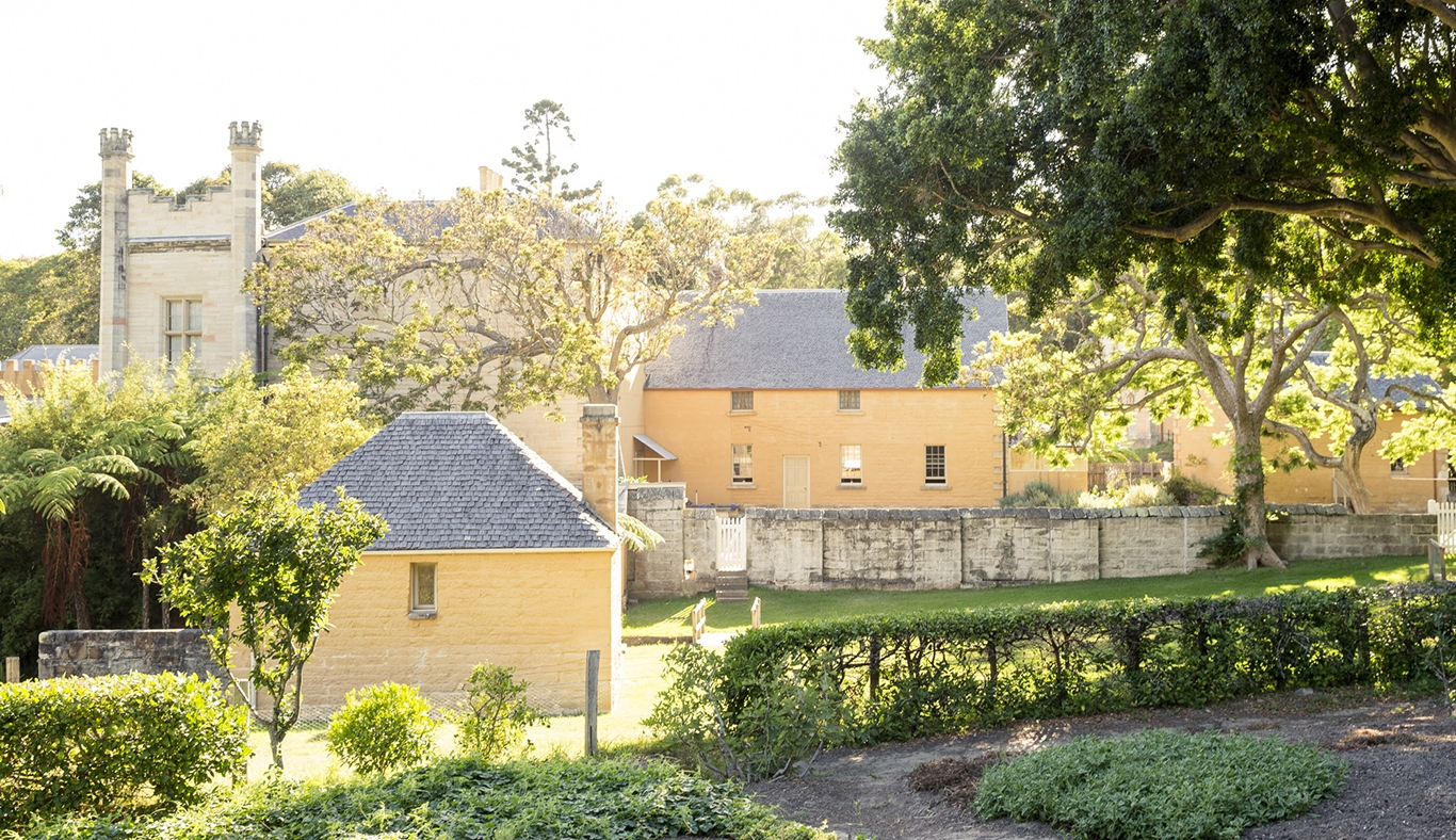 The yellow buildings of Vaucluse House surrounded by trees