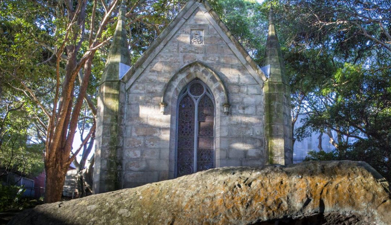 A grey stone mausoleum set in shadows behind a large rock