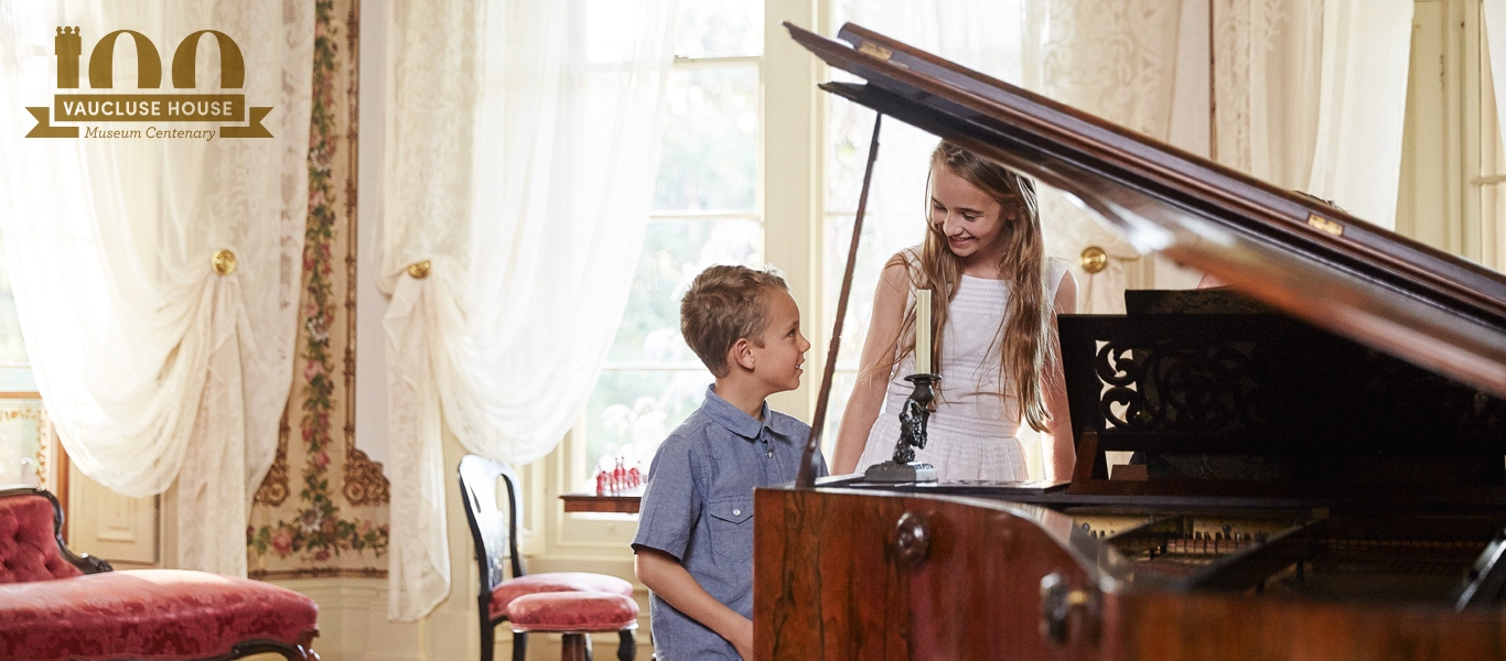 Two children, one seated, at piano in drawing room.
