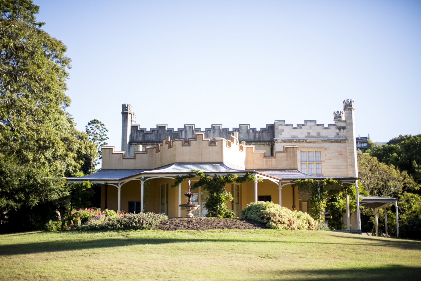 View across lawn to house with crenellated facade and verandah.