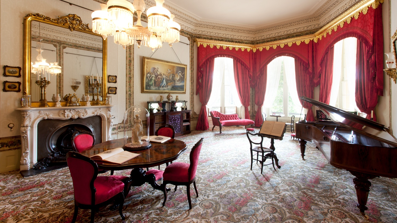 Drawing room looking from distance at table, chairs and drapes on windows.