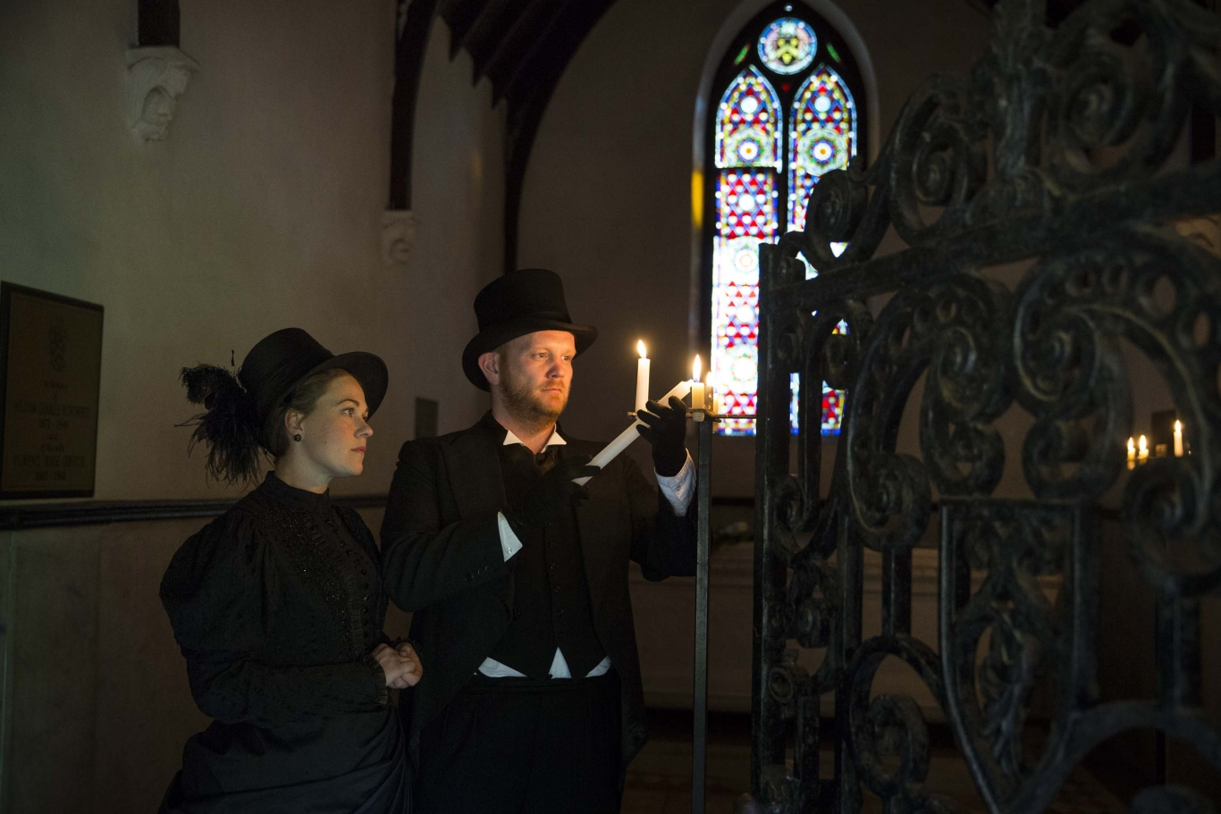 Colour image of a man and woman lighting candles inside the sandstone mausoleum. A they are backlit by a stained glass window.
