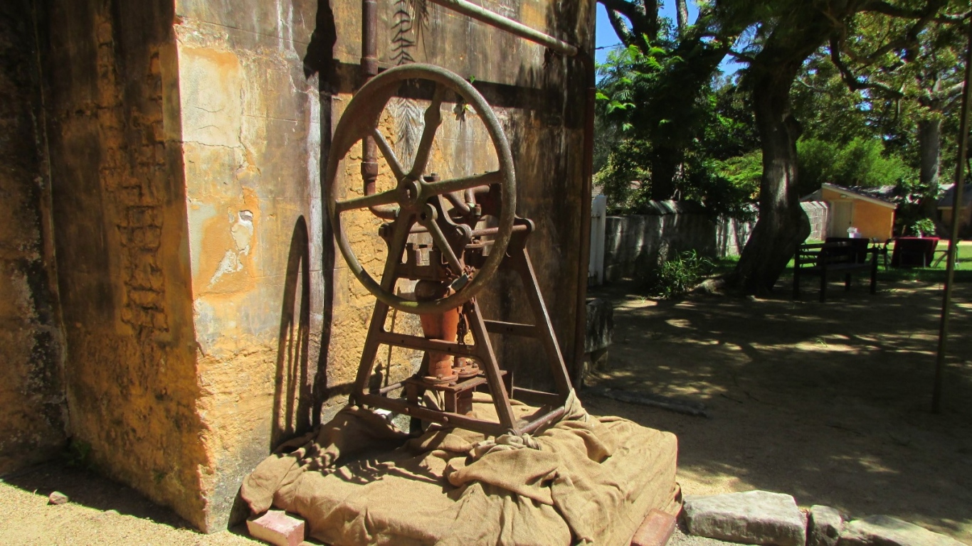 Old pump outside house with hessian wrapped base with garden in background.
