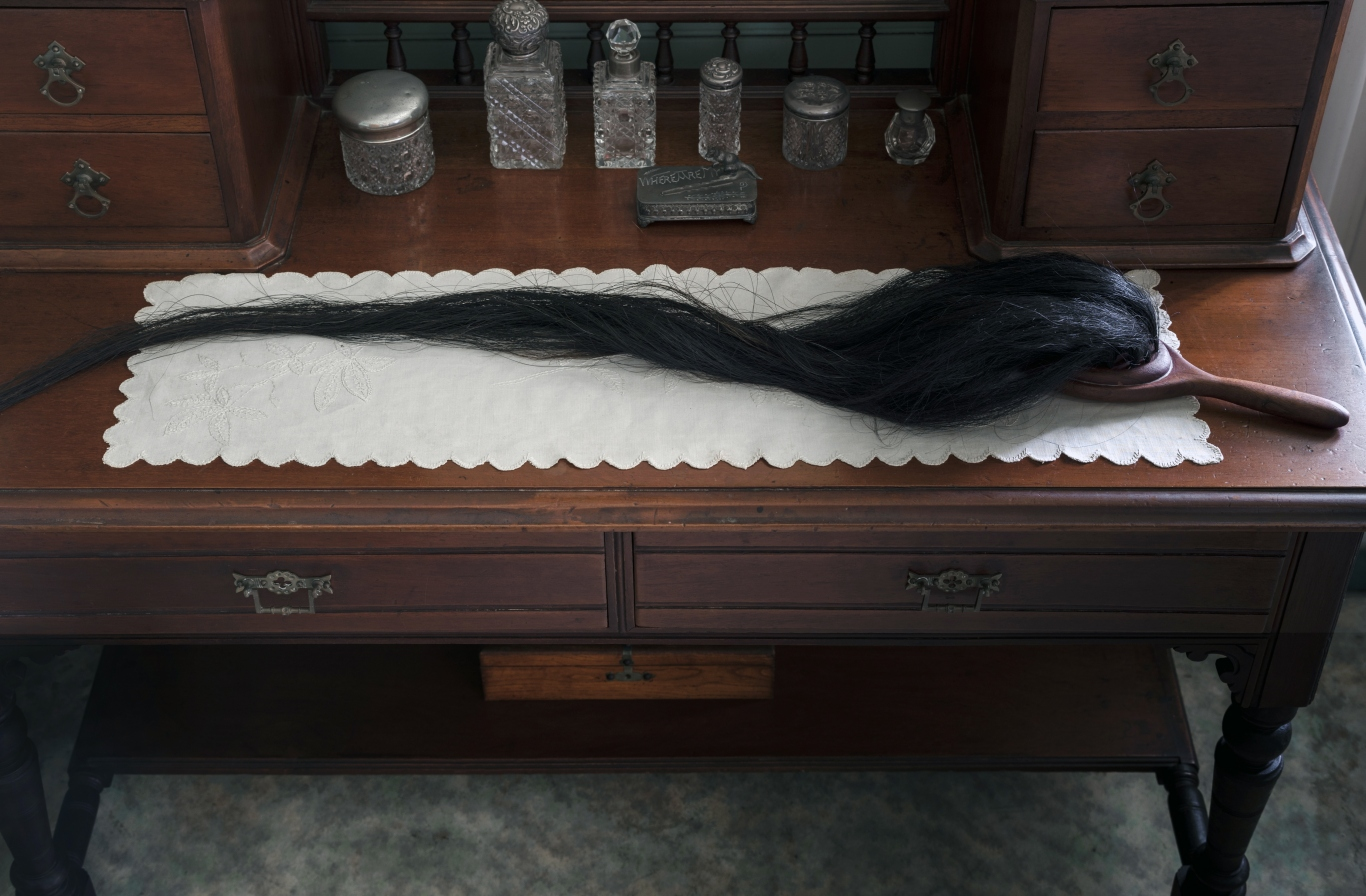 Wooden hairbrush with actual hair for bristles on table.