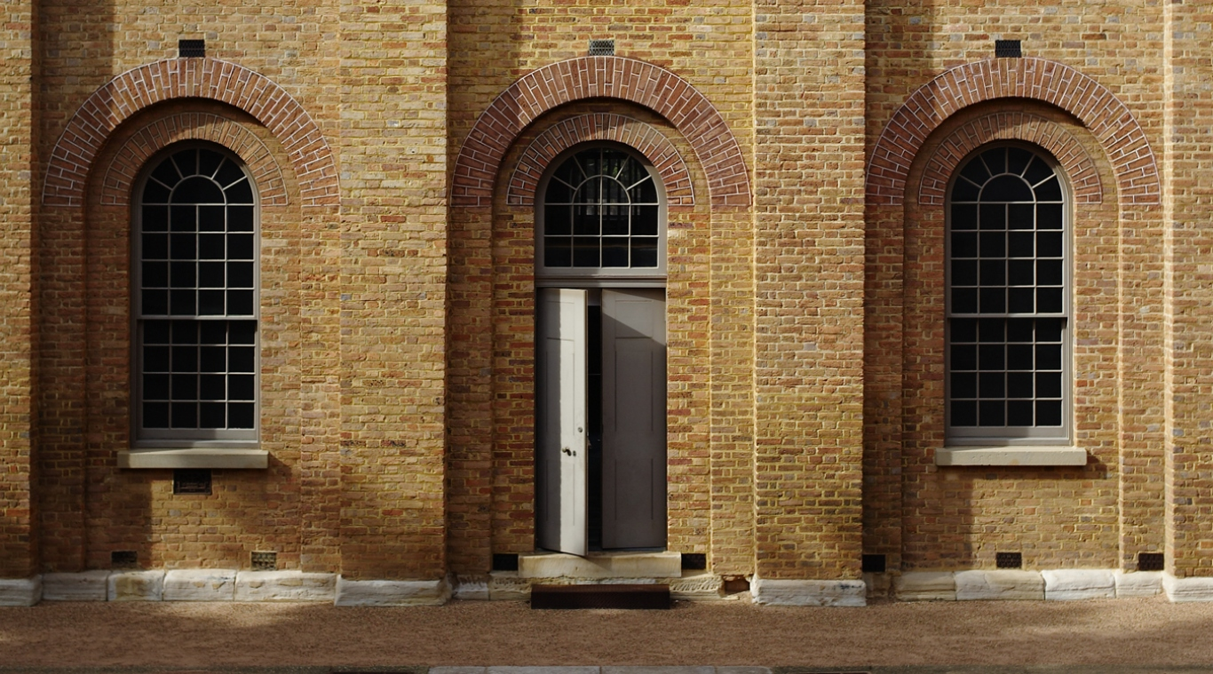 Open arched doorway framed by two arched windows set in brick barracks wall.