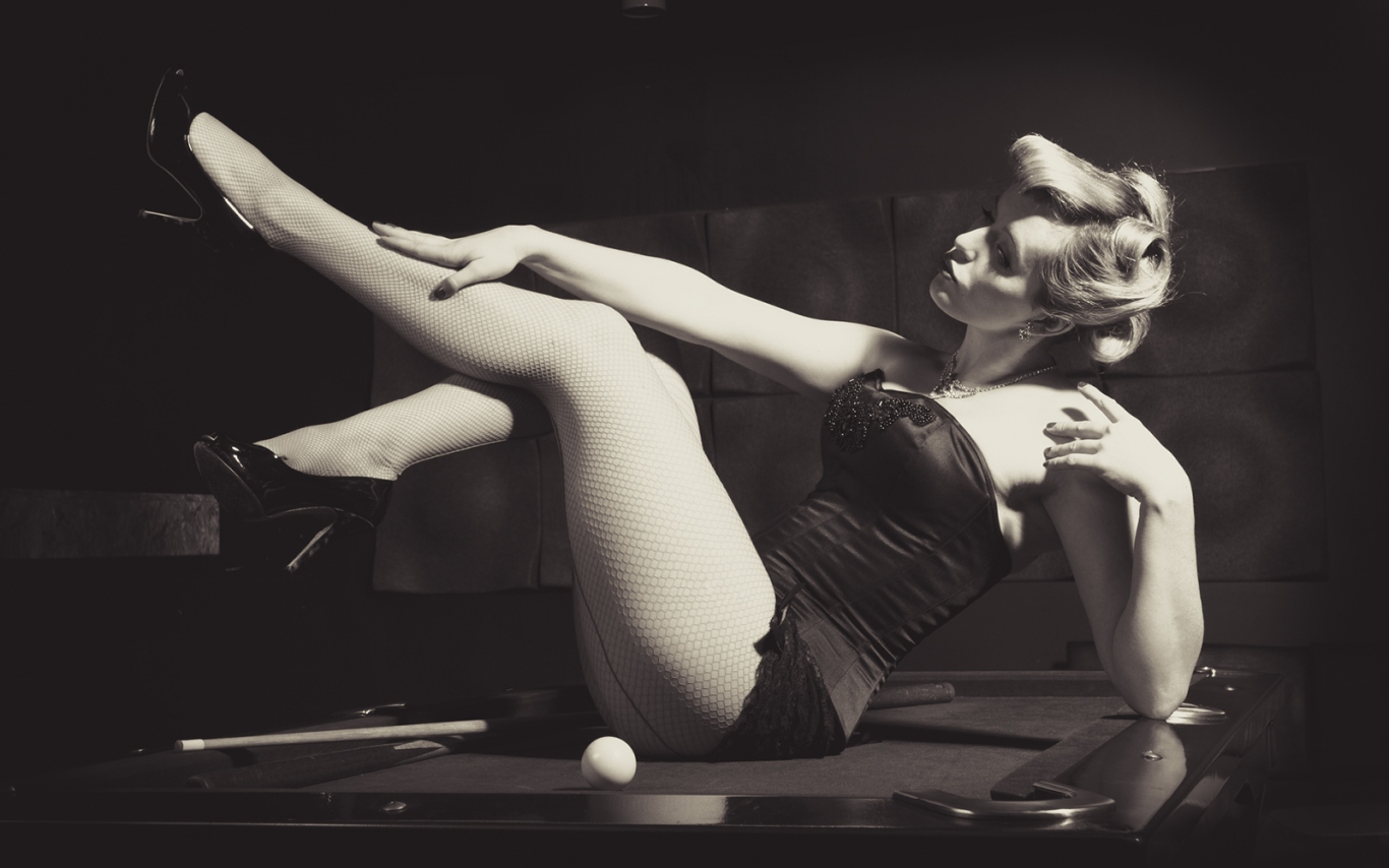 Woman in fishnet stockings and black Satin on a billiard table