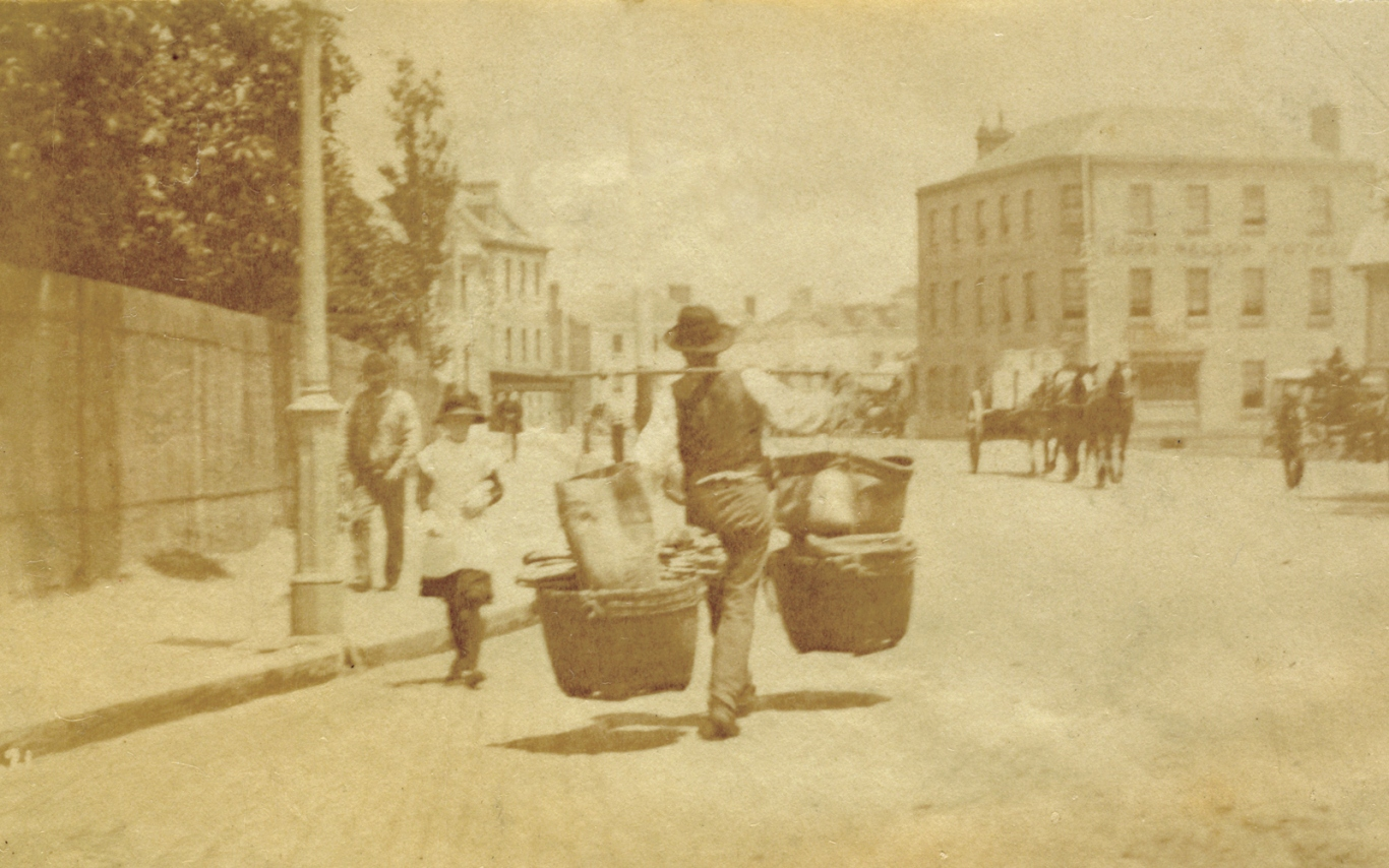 Hawker in the street at the Rocks carrying large baskets of goods