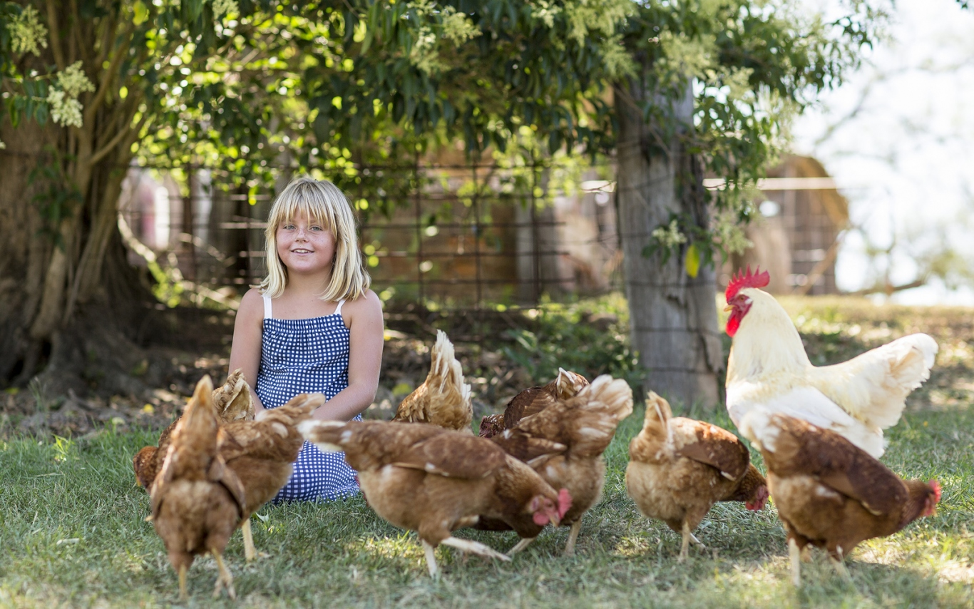 Girl sitting in garden with chickens