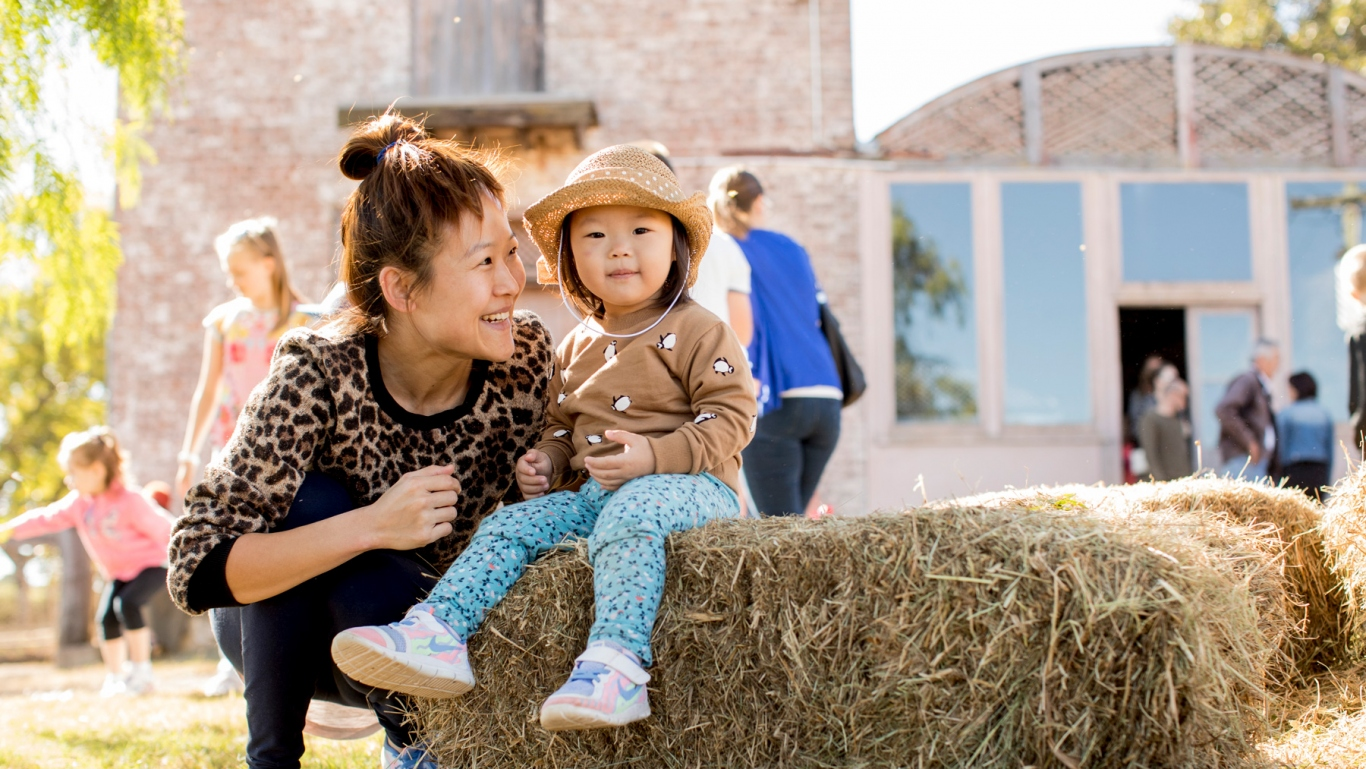 Woman with child sitting on hay bale in outdoor setting.