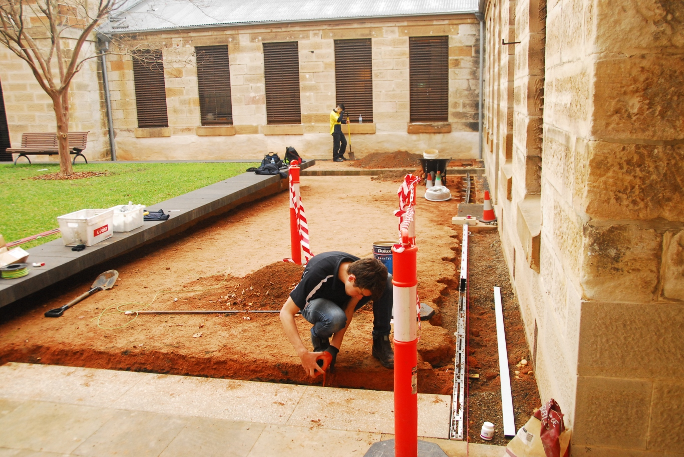Excavtion with two men working in crouched position with lawn and sandstone building in background.