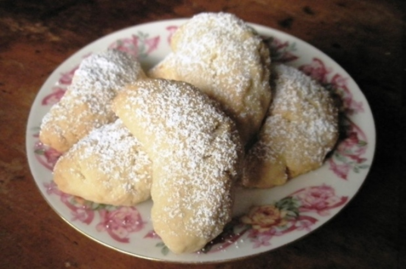 Plate of biscuits with icing sugar dusted on top.