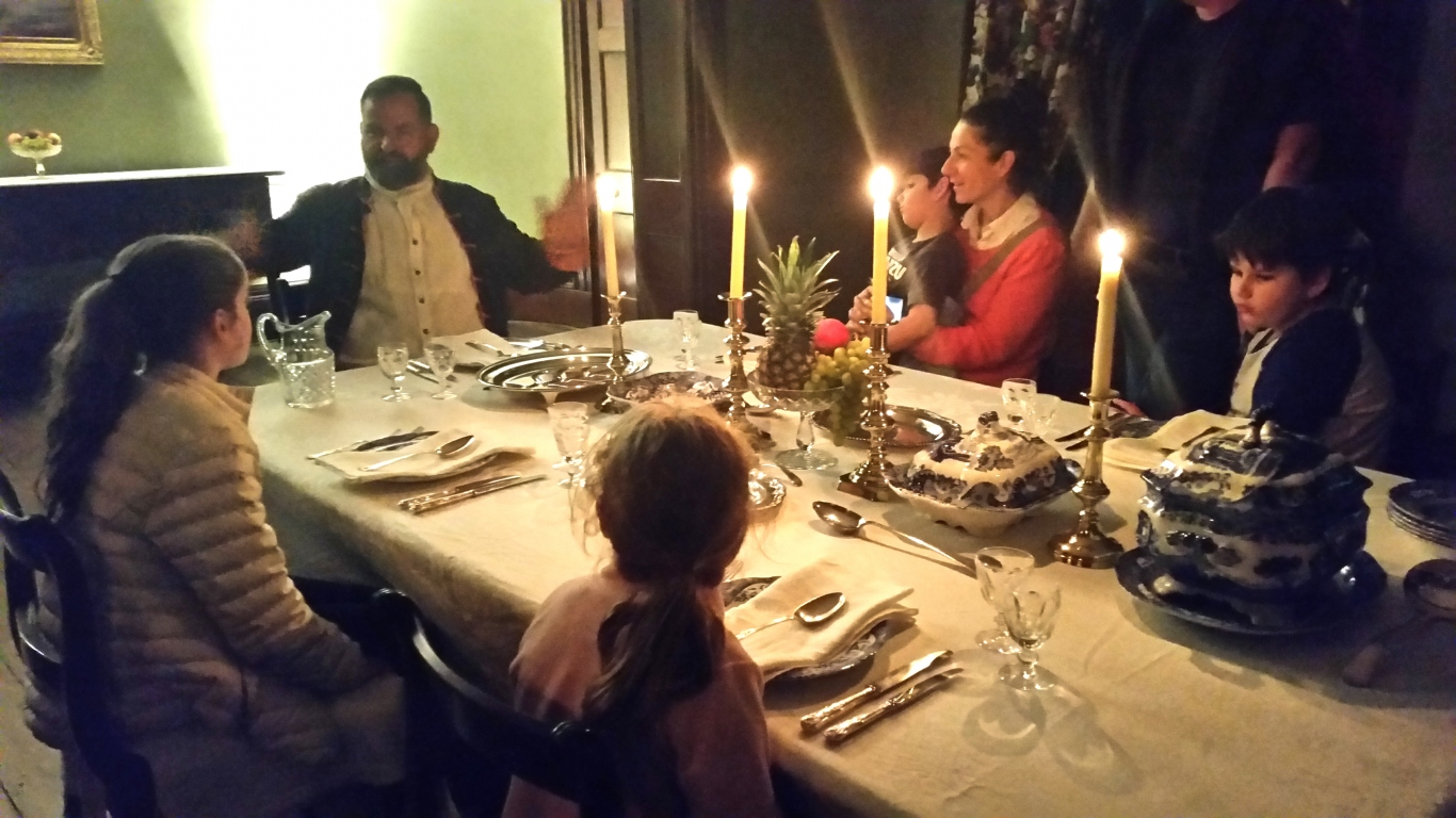 Group seated around candlelit table.