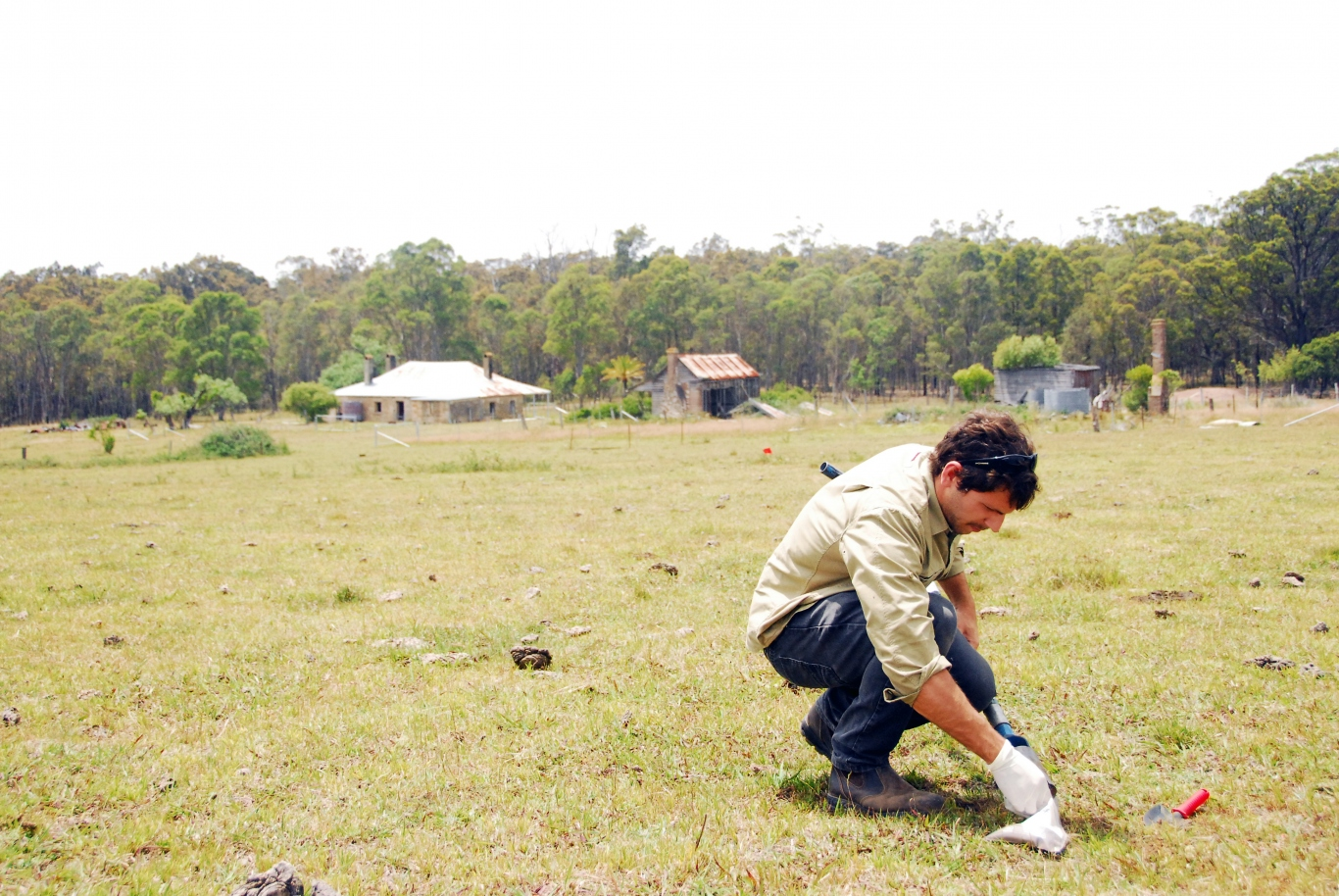 Man squatting in foreground taking samples from pasture, with house and outbuildings with bush in background.