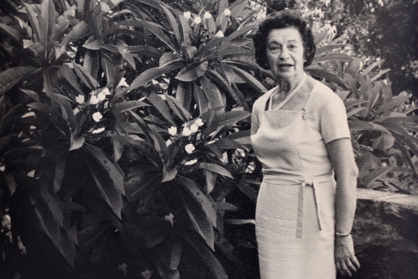 Black and white image of woman standing in front of bush in garden.