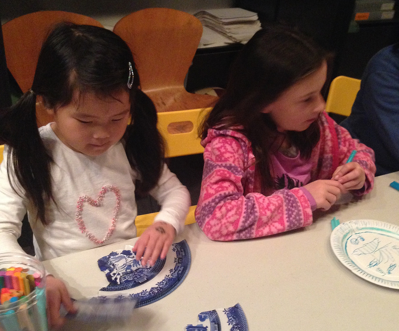 Two girls working on puzzle and drawing activities.