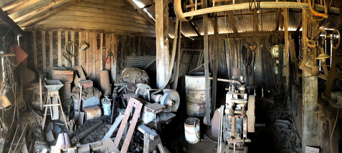 Panoramic view of interior of wooden building with a collection of farming and other items.