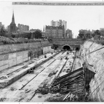 Black and white view of tracks leading into tunnels.
