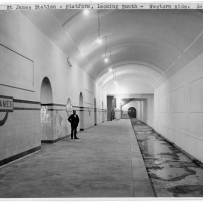 Interior of tunnel with platform, figure in middle distance.