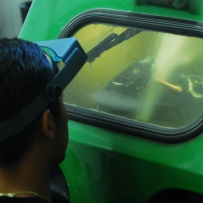 Man wearing blue welding goggles at glass screen of chamber.