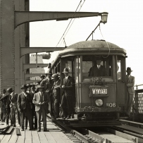 People file onto a tram waiting on the outside lane of the Harbour Bridge