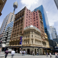 Exterior view of corner Victorian style building dwarfed by surrounding high rise