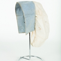 Blue and white hair cover on stand.