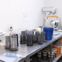 Set of steel cylinders on metal benchtop.