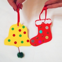 A yellow bell and a red stocking-shaped decoration, held by hands against white background.