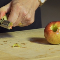 Hand holding corer with core in it, next to apple on wooden table.