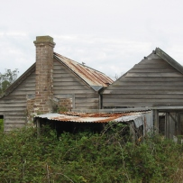 In this image both the front and rear gabled sections of the house are standing, although in a bad state of repair
