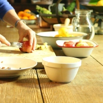 Hands pricking apple with fork on table with other ingredients and equipment.