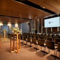 Interior of room set up for conference with screen visible in background.