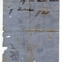 Back of worn paper form with handwritten note.