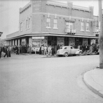 Outside of the Auburn Hotel showing a car and crowd gathered on the footpath