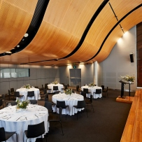 Large room with curved timber roof set up for event with round tables set for meal.