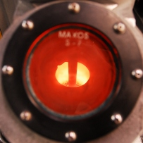 Red and gold glowing interior of heated round crucible.