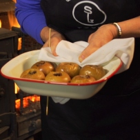 Woman's hands holding white baking dish containing six baked apples.