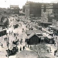 View across Circular Quay showing wide roads with people, trams and tram lines crossing the space.