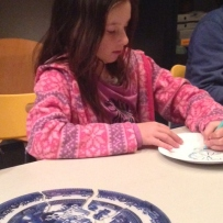 Girl with long hair and wearing a pink top drawing on paper plate with colour design.