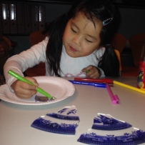 Young girl with pigtails drawing on paper plate with colour design.