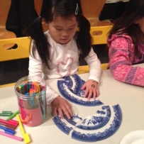 Young girl with pigtails doing plate puzzle.